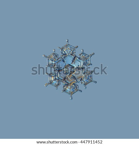 Snowflake isolated on pale blue background: macro photo of real snow crystal, captured on glass with LED back light. This is small stellar dendrite snowflake with relief surface and short arms. - stock photo
