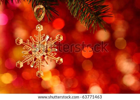 Snowflake on branch of Christmas tree against red blurred background - stock photo
