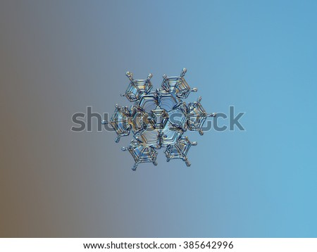 Snowflake on smooth gradient background: macro photo of real snow crystal on glass surface with LED back light. This is rare, medium size 12-sided snowflake. - stock photo