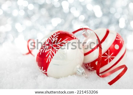 Snowflake on snow against holiday lights background.