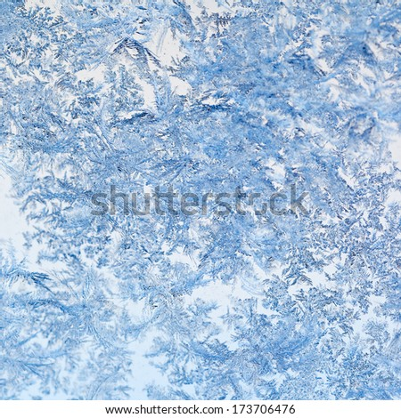 snowflakes and frost on glass close up - frosty blue pattern on window in cold winter day - stock photo