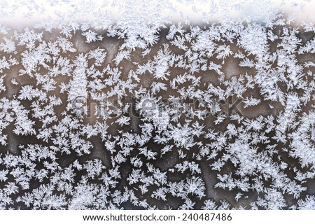 snowflakes and frost pattern on window pane in cold winter evening - stock photo