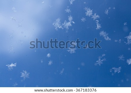 Snowflakes on glass. Snowflakes falling. Winter background. Hoar-frost background. Winter background with snowflakes festival illustration, glass background and motion blur. - stock photo