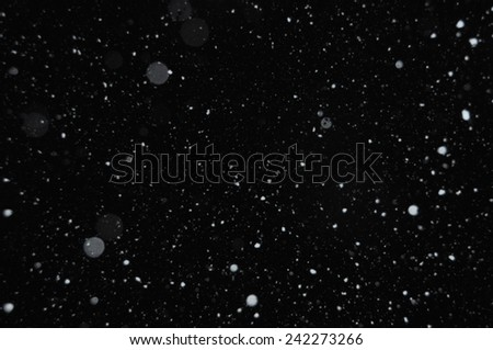 Snowflakes on winter sky. Snow storm abstract background blur. - stock photo