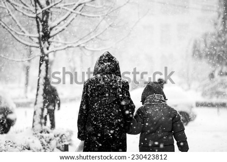 Snowing urban landscape with people passing by