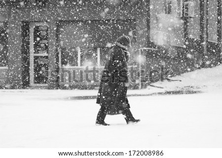 Snowing urban landscape with woman passing by  - stock photo