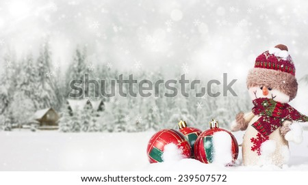 Snowman and red Christmas balls in the snow, snowy pine trees in the background - stock photo