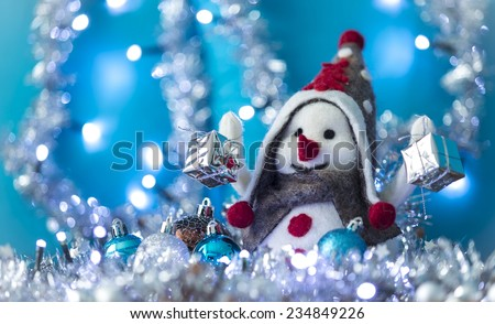 Snowman between Christmas balls smiling brought Christmas gifts, turquoise background with flashing lights - stock photo