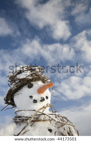 Snowman close-up with scarf and hat made from natural plant materials with big blue sky area above - stock photo