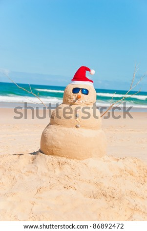 Snowman made out of sand with ocean in background. Sandman is wearing Sunglasses and santa hat could be used for christmas cards & global warming concepts - stock photo