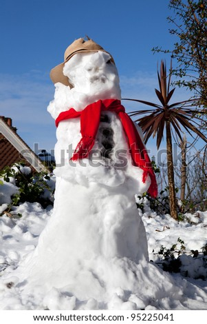 snowman melting with palm tree in background. seasonal snow sculpture with scarf and hat - stock photo