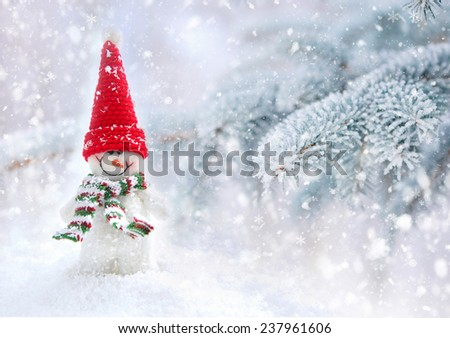 Snowman on a background snow-covered fir branches - stock photo