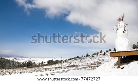 Snowman on Wooden Deck Overlooking a Valley - stock photo