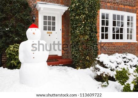 Snowman outside house - stock photo