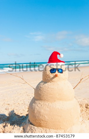 Snowman´s friend Sandman On holiday trip at the beach. He is wearing sunnies, santa hat and has a carrot as nose - stock photo