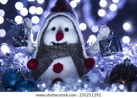Snowman smiling brought Christmas gifts, blue background with flashing lights - stock photo