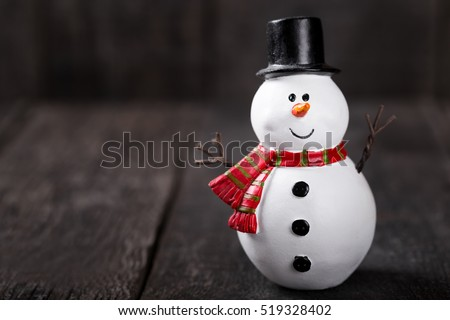 Snowman toy on rustic wooden background. Christmas and New Year celebration