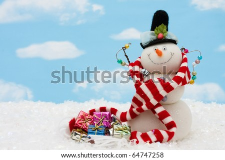 Snowman wearing scarf on blue sky background, merry Christmas - stock photo