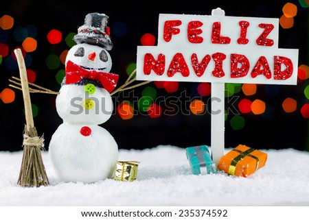 Snowman with a Merry Christmas signpost written on spanish, bokeh lights - stock photo