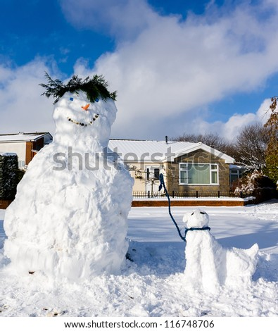 Snowman with a pet snow dog under a blue sky on a crisp winter's day - stock photo