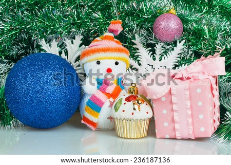 Snowman with blue ball, pink gift box and white snowflake on a background of green garland - stock photo