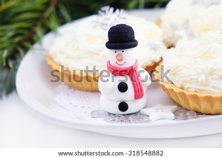 Snowman with cake on the plate, Christmas background.