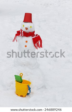 Snowman with red bucket over snowy back - stock photo