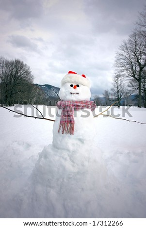 Snowman with Santa hat, scarf, and winter landscape background. - stock photo