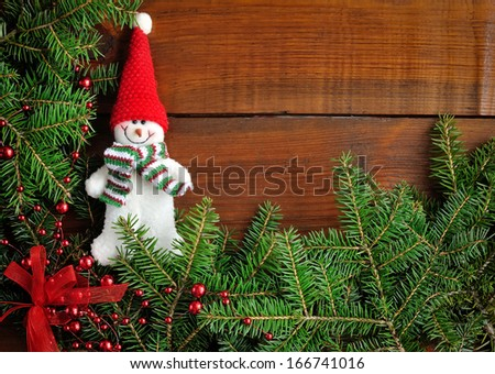 Snowman with the branches of fir on wooden background - stock photo