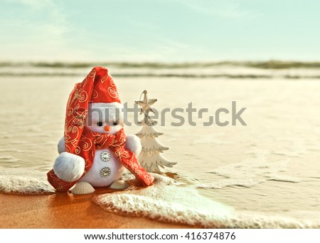 Snowman with white Christmas tree on the sea shore - stock photo