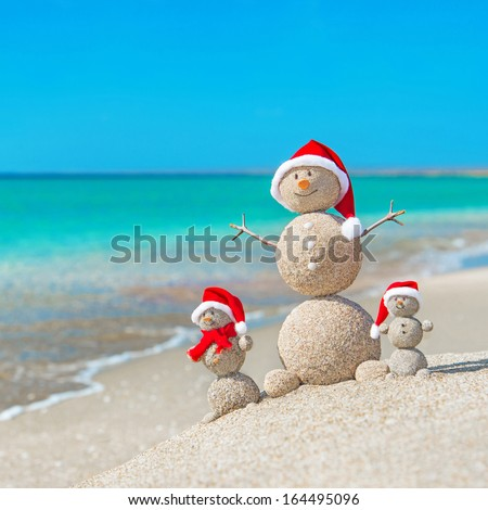 Snowmans family at sea beach in santa hats. New years and christmas holiday in hot countries concept. - stock photo