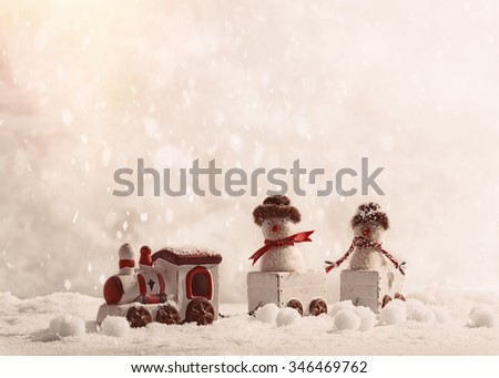 Snowmen sitting in toy train set at Christmas in the snow - stock photo