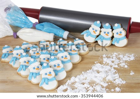 Snowmen Sugar Cookies On A Wood Table With Blue And White Royal Icing In Decorating Bags