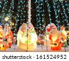 Snowmen surrounded by christmas lights. - stock photo