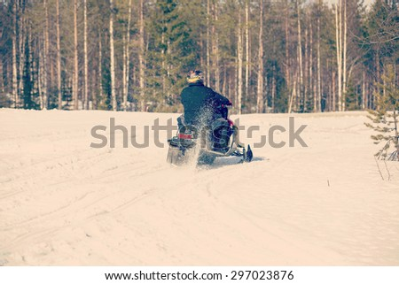 Snowmobile is accelerating in the sunshine. Image has a vintage effect.