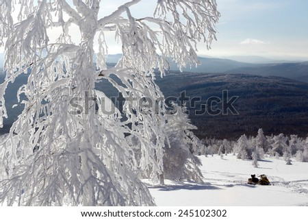 Snowmobile stands in deep snowdrifts of the mountains of the Southern Urals. - stock photo