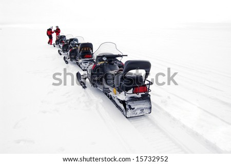 snowmobile stop in a single file in the snowfield.