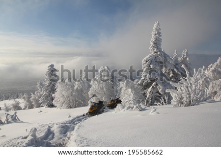 Snowmobiles and forest, mountain - stock photo