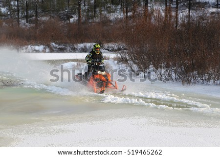 Snowmobiles  will boost ice crust on the river in South Yakutia, Russia