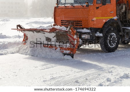 Snowplow removing snow from city road