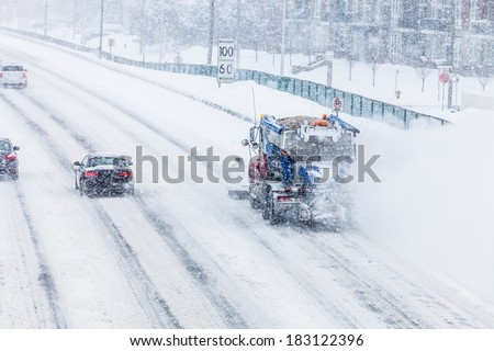 Snowplow Truck Removing the Snow from the Highway during a Cold Snowstorm Winter Day - stock photo