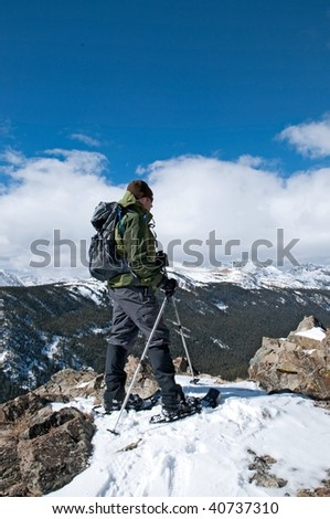 Snowshoer on a summit, looking at snowy mountains peaks - stock photo