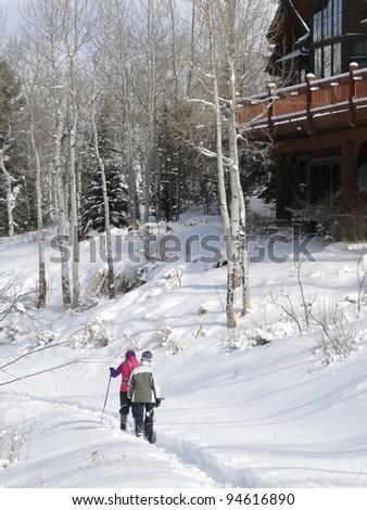 Snowshoers on winter trail near large modern homes inCordillera,Colorado - stock photo