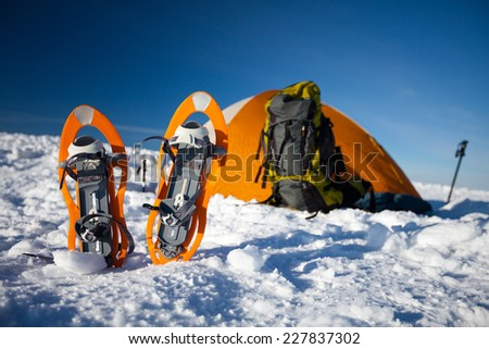 Snowshoes at the orange tent on sunny day in wintertime - stock photo