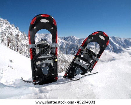 Snowshoes in a deep drift on a California mountain peak. - stock photo