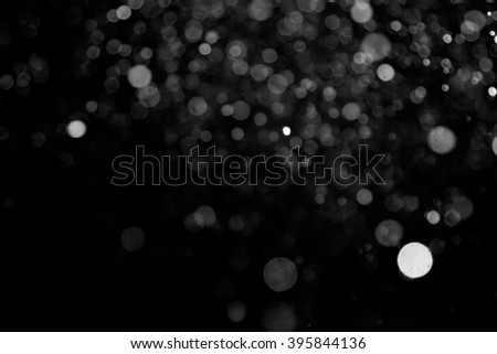 Snowstorm texture. Bokeh lights on black background, shot of flying snowflakes in the air - stock photo