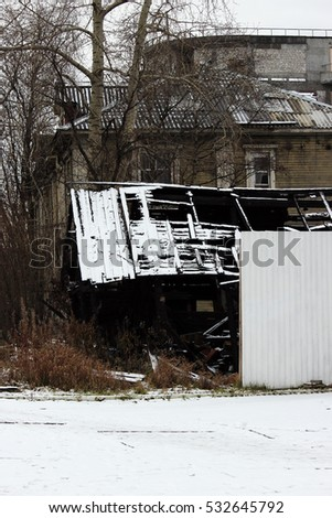 Snowy abandoned burned-out fire wooden black house