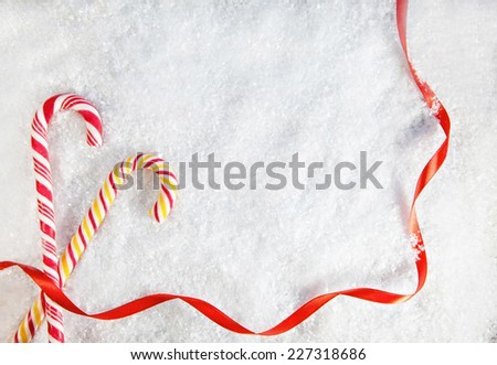 Snowy Background With Two Candy Canes . Copy Space - stock photo