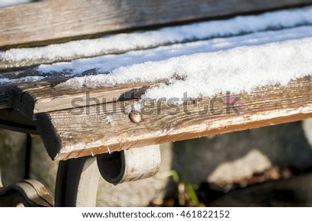 Snowy bench in the public park.