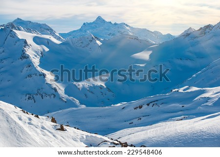 Snowy blue Caucasian mountains in clouds. Winter landscape - stock photo